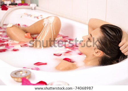 Attractive naked girl enjoys a bath with milk and rose petals. Spa treatments for skin rejuvenation - stock photo