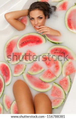 Attractive naked girl enjoys a bath with milk and slices of watermelon. - stock photo