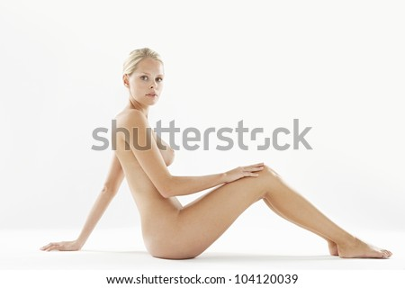 Attractive naked woman isolated on a white background, looking at camera while leaning back on her hand. - stock photo