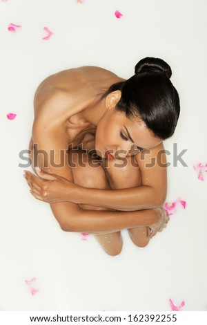 Attractive naked woman lying in a milk-bath. Up front view. - stock photo