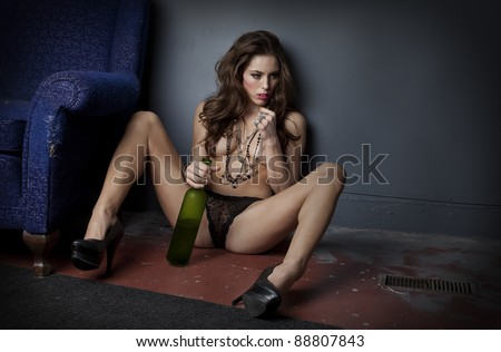 Attractive nearly-naked woman seated on grungy floor holding half empty bottle of wine between her legs. - stock photo