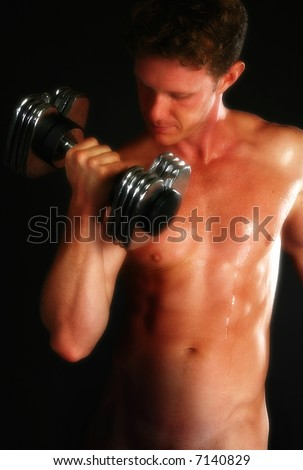 Attractive nude male lifting weights over black background. - stock photo