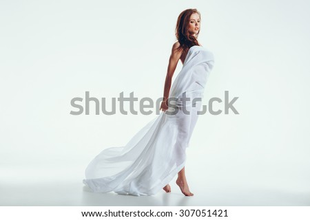 Attractive nude woman with a white fabric on her body posing over white background. Caucasian female model standing wrapped in transparent scarf. - stock photo