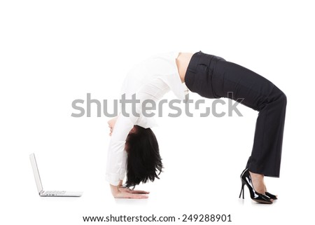 Attractive office employee, beautiful young female in formalwear standing in yoga position Chakrasana, Urdva Dhanurasana, Upward Bow (Wheel) Pose in front of laptop on white background, isolated - stock photo