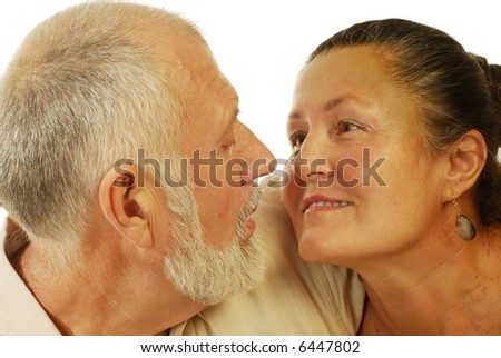 Attractive older couple looking at each other lovingly; isolated on white - stock photo