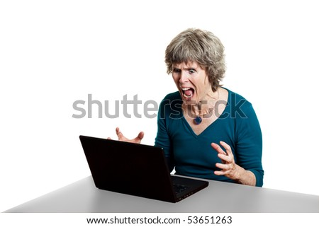 Attractive older lady with laptop problems, shouting at her PC - stock photo