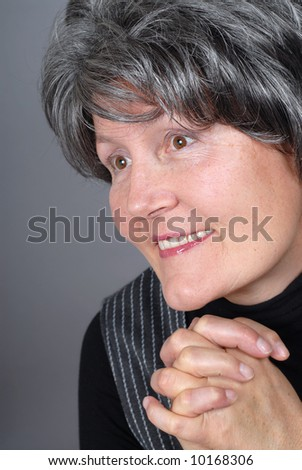 Attractive older woman beaming with hope and optimism - stock photo