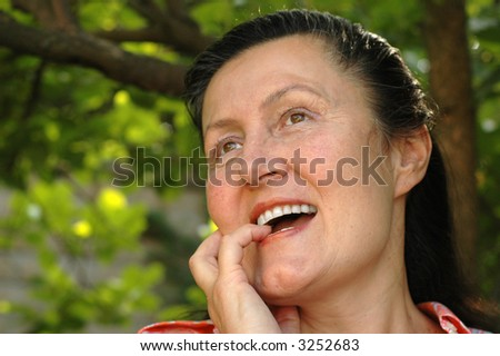 Attractive older woman enjoying a moment of peace in her garden - stock photo