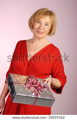 attractive older woman in red dress holding a wrapped gift - stock photo