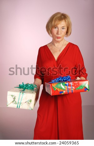 attractive older woman in red dress holding gifts - stock photo
