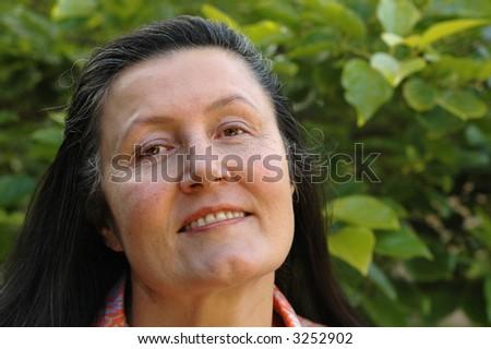 Attractive older woman relaxing in her garden - stock photo