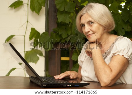 Attractive older woman sitting at a table at home on the veranda