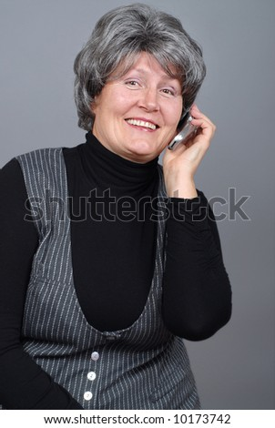 Attractive older woman talking on the phone and laughing - stock photo