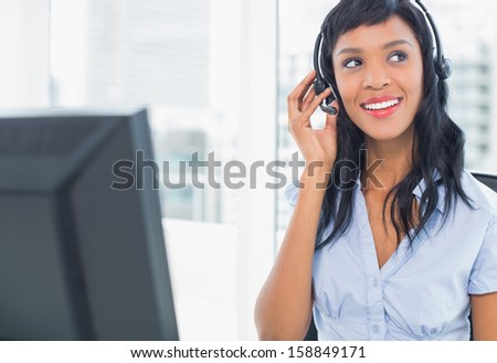 Attractive operator adjusting her headset in office - stock photo