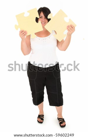 Attractive over weight forty year old french American woman holding two large wooden puzzle pieces over white background.