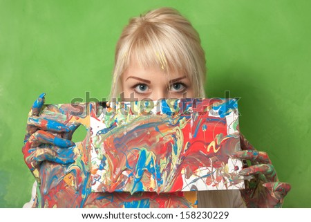 Attractive painter shows her abstract and impulsive painting - stock photo