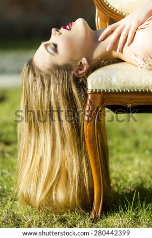 Attractive passionate girl with beautiful long hair lying on sofa looking up holding hands on neck in peach evening dress in sunset on natural background outdoor, vertical picture - stock photo