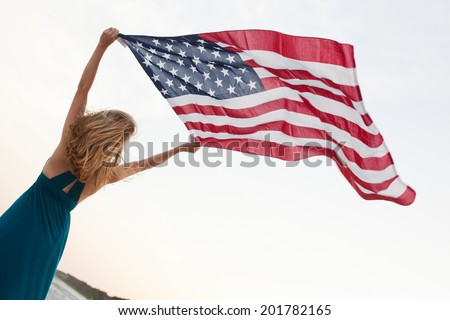 Attractive patriotic young woman holds American Flag above head while standing on the beach