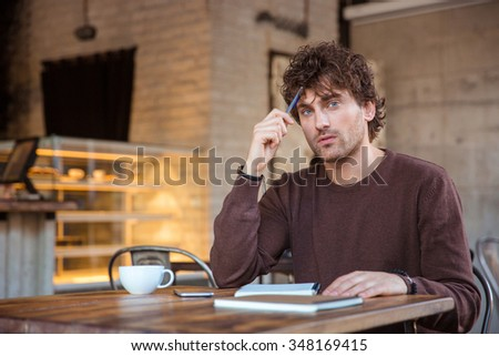 Attractive pencive handsome thoughtful curly young male in brown sweetshirt sitting in cafe with notebook and thinking - stock photo