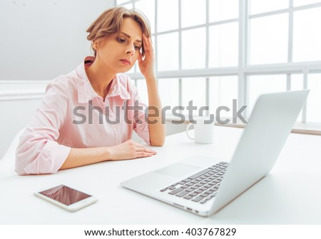 Attractive pensive business woman in classic shirt is using a laptop while working in office