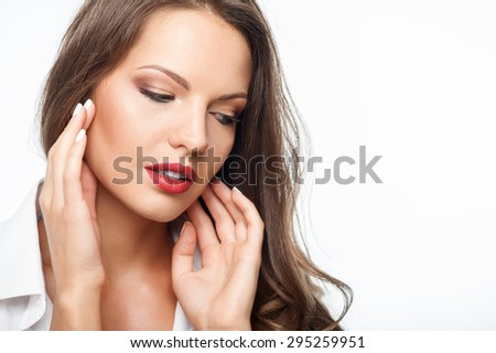 Attractive pensive woman is touching her face thoughtfully.  She is looking down with sadness. Isolated on background and copy space in right side - stock photo
