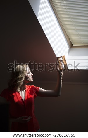 Attractive pensive young blonde woman with curly hair in red red blouse standing in office near window holding clock and looking on time at sand glass indoor, vertical picture - stock photo
