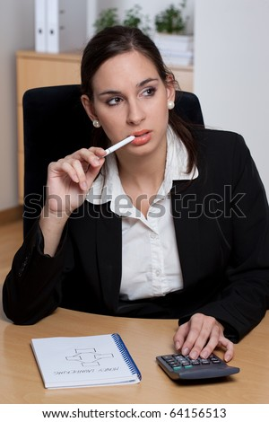 Attractive pensive young businesswoman making calculations and business plans