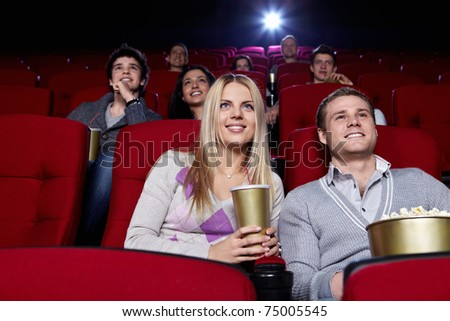 Attractive people are watching a movie at the cinema - stock photo