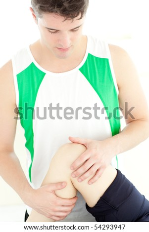 Attractive physical therapist checking a woman's knee during a medical exam - stock photo