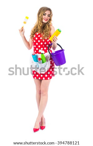 Attractive pin-up girl in red dress with polka dots. Cleaning the house. Housewife with accessories for cleaning on a white background. Retro style. Fashion.