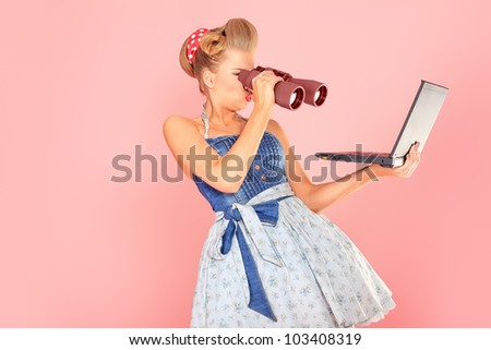 Attractive pin-up girl looking through binoculars to her laptop. - stock photo