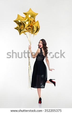 Attractive playful happy woman with retro hairstyle in classic black dress and shoes looking back and holding golden balloons - stock photo