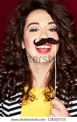 Attractive playful young woman holding mustache on a stick - stock photo