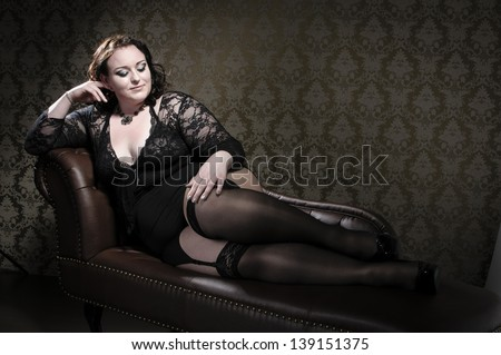 Attractive plus size model wearing black lace lingerie, lying an a brown chesterfield sofa. - stock photo