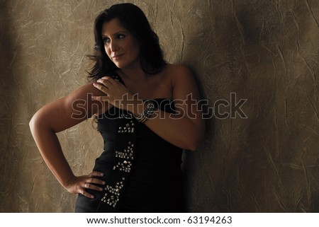 Attractive plus-sized fashion model wearing black party dress in studio setting. - stock photo