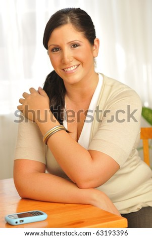 Attractive plus-sized model sitting at table with cell phone close at hand. - stock photo