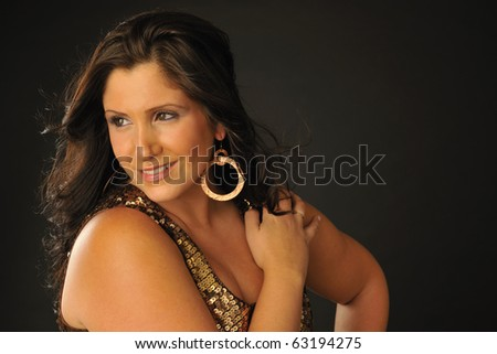 Attractive plus-sized model wearing gold party dress in studio setting. - stock photo