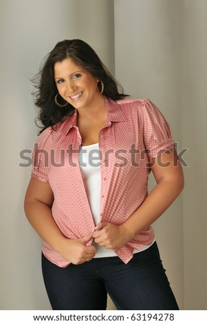 Attractive plus-sized woman wearing red blouse in studio setting. - stock photo