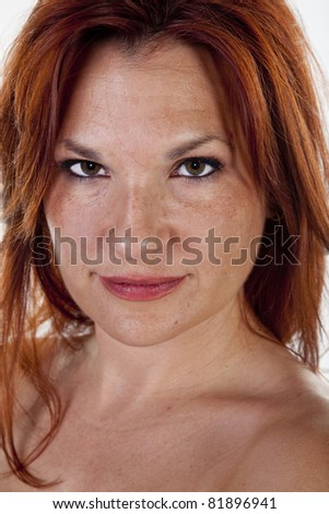 Attractive portrait of a red-haired woman on a white background.
