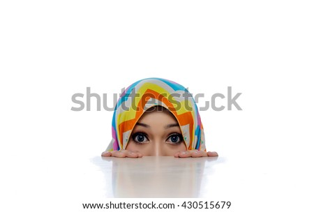 Attractive portrait of young muslim woman faces peeked from under the table - stock photo