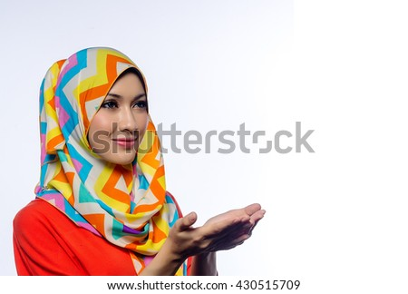 Attractive portrait of young muslim woman in head scarf smile, spreads out hands while praying