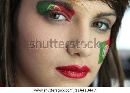 Attractive Portuguese woman with national flag painted on face