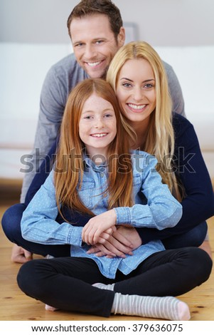Attractive positive happy young family posing behind each other sitting cross legged on the living room floor smiling at the camera, pretty little girl in the foreground