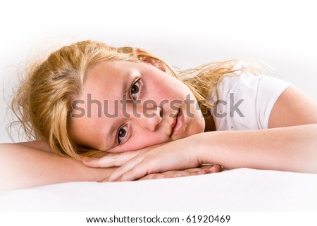Attractive pre-teen girl looking intensely at viewer, laying down - stock photo