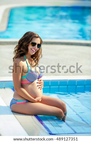 Attractive pregnant woman on holiday at sea, the pool, in the countryside.