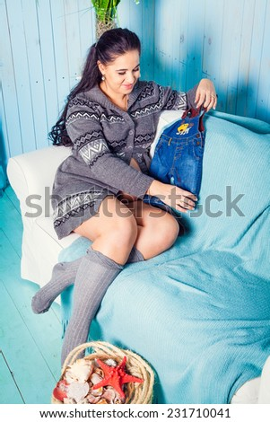 Attractive pregnant woman touching her belly and sitting on couch - stock photo