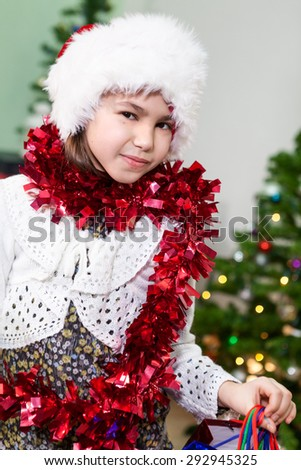 Attractive preteen girl in Santa hat and tinsel, portrait, looking at camera - stock photo
