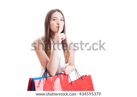 Attractive pretty shopaholic with shopping bags making a silence gesture as quiet or shush concept isolated on white studio background with copyspace - stock photo