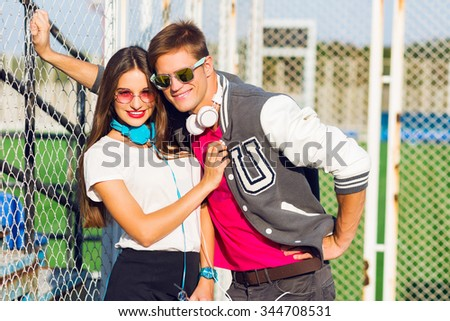 Attractive pretty young hipster couple posing on sunny summer day outdoor, wearing bright trendy teenager outfit , listening music and drink juice , athletic field background.