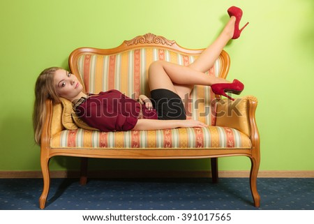 Attractive pretty young woman laying on vintage retro sofa couch. Elegant fashionable gorgeous girl wearing maroon shirt and skirt. Fashion. - stock photo